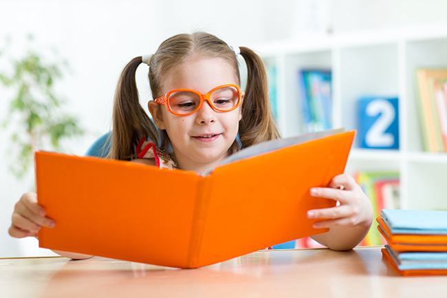 Child little girl reading a book at home or primary school; Shutterstock ID 248572540; PO: mw/polish coalition